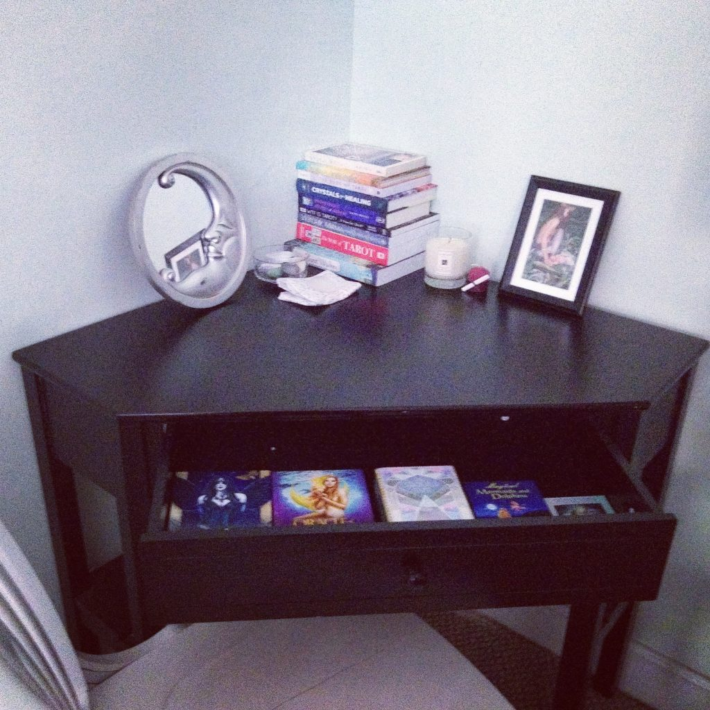 Black corner desk with books, crystals, and tarot and oracle decks